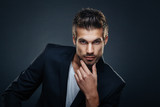 Portrait of handsome man in a studio on a dark background - 93565474
