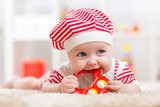 Fototapety Cute baby in hat on the bed having fun