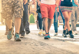 Fototapety Crowd of people walking on the street - Detail of legs and shoes moving on sidewalk in city center - Travellers with multicolor clothes on vintage filter - Shallow depth of field with sunflare halo