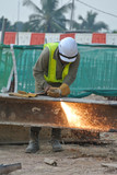 Construction workers cutting metal using blowtorch at the construction site poster