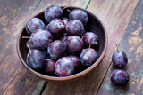 Plums in a bowl on the wooden table