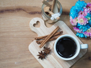 black coffee cup and cinnamon with spicy herb on wooden tray
