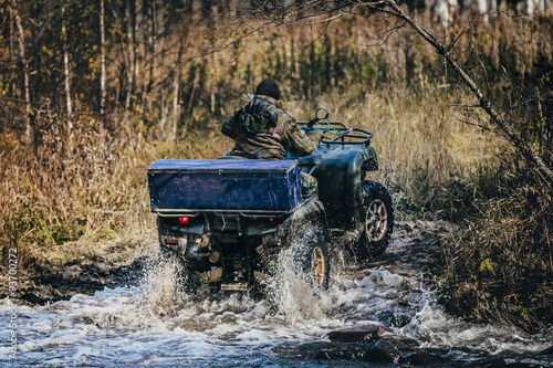 Poster Forester ATV rides through autumn forest through a river crossing
