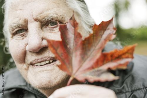 Poster Seniorin hält ein herbstliches Blatt, Herbst, Natur,Park