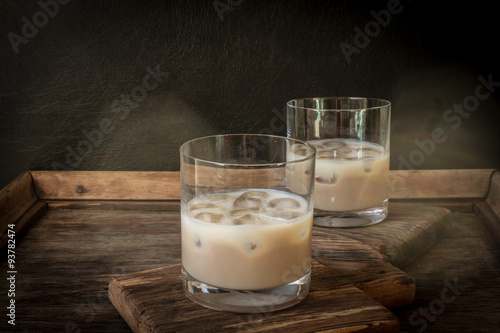 Irish cream liqueur in a glass with ice. Poster
