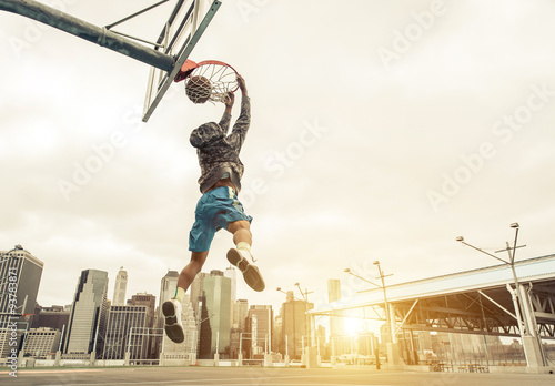 Zdjęcia Basketball street player making a rear slam dunk. New york and Manhattan buildings in the background