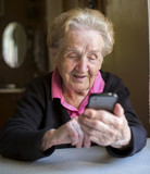 Elderly woman typing on the smartphone. Grandma.