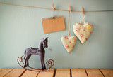 vintage rocking horse next to fabric hearts and empty card for adding text hanging on the rope on wooden floor. retro filtered image