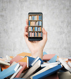 A hand holds a smartphone with a book shelf on the screen. A heap of colourful books. A concept of education and technology. Concrete wall background.