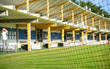 Golf driving range with golfer through protective net. Selective focus on net.