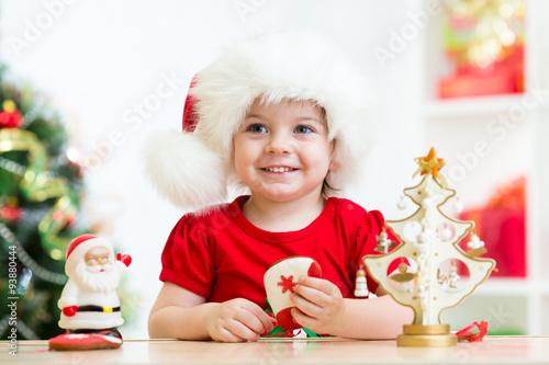 Fototapeta Little girl child wearing a festive red Santa hat with Christmas
