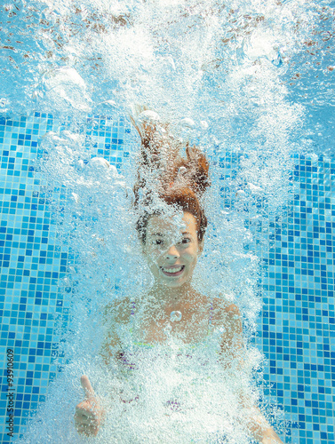 Poster, Tablou Girl jumps and swims in pool underwater, happy active child has fun in water