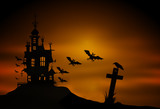 Silhouette of a castle and flying bats over the cemetery on a stormy night