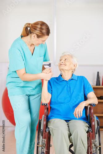 Leinwanddruck Bild Krankenpflegerin hält Hand einer alten Frau