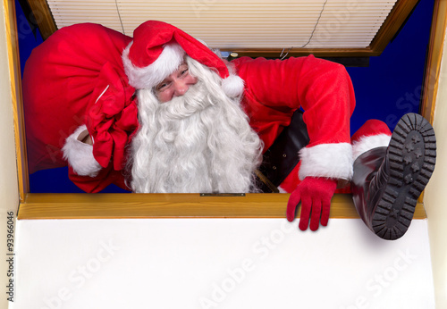 Poster Santa Claus carrying a bag of gifts and climbs into the room through the window