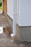 New rain gutter and downspouts on house construction with puddle. Close up on wet house foundation. poster