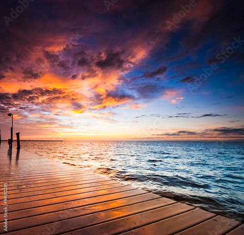Foto op Canvas Zee zonsondergang Burning sunrise at the ocean, sunlight reflecting on the wet wooden dock. Summer travel concept