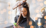 Fototapety happy woman with stylist making hairdo at salon
