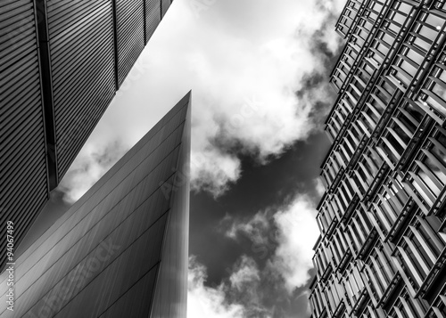 Black and white image of steel and glass skyscrapers of London against a cloudy sky
