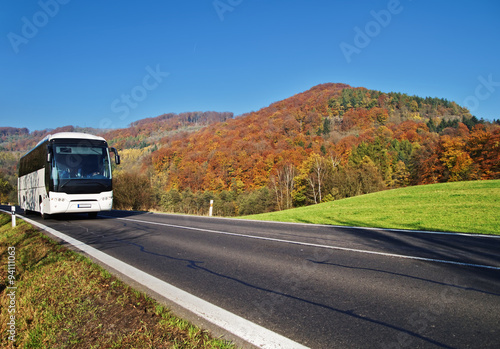 Poster White Bus arriving at the asphalt road through the valley below the wooded mountain of glowing autumn colors