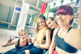 Fototapety Happy girlfriends group taking selfie in gym dressing room - Sporty female friends ready for fitness time - Healthy lifestyle and sport concept in training center - Bright vintage desaturated filter