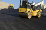 Road roller leveling fresh asphalt pavement with space for your text.