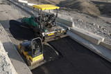 Tracked paver laying asphalt while steamroller flattening