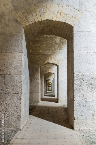 Castle tunnel interior with a series of symmetric arches in a bastion fortress. - 94178263