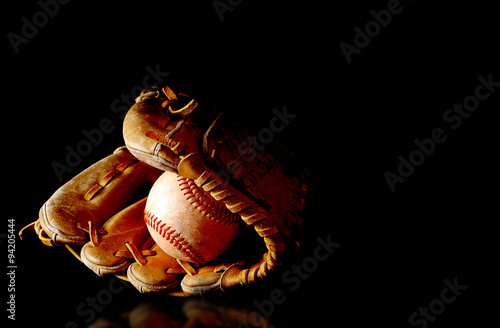 Old baseball glove and rough ball with side lighting on black