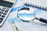 Magnifying glass, calculator and pen on financial graph