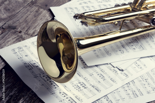 Trumpet and sheet music on old wooden table. Vintage style. - 94208439