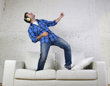 Fototapeta 20s or 30s man jumped on couch listening to music on mobile phone with headphones playing air guitar