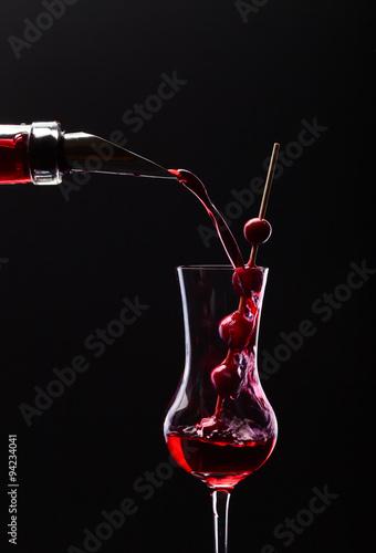 Fototapeta cranberry liquor on black background