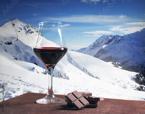 Wine glass and chocolate with winter mountainscape Poster