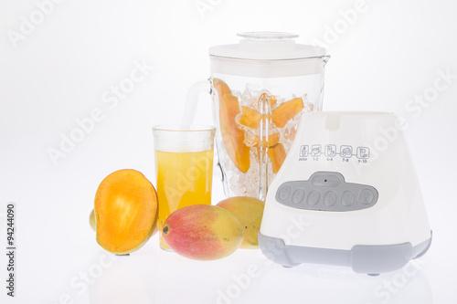 Licuadora, con fruta y jugo sobre fondo blanco.