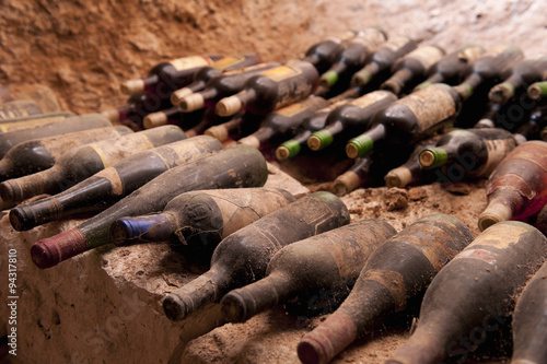 Old wine bottles on a stone step, a cave Poster