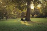 Man sitting under a pine tree - 94320434