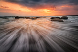 Sea sunrise. Stormy sea beach with slow shutter and waves flowing out