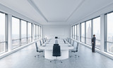 A Businessman is looking out the window in a modern panoramic meeting room in New York. The concept of the meeting of the Board of Director of the huge transnational corporation.