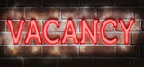 """Illustration showing a neon """"vacancy"""" sign on a brick wll"""