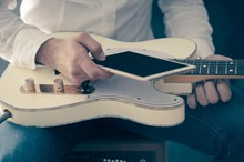 Man using mobile device and guitar