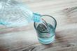 bottiglia versa acqua in un bicchiere di vetro trasparente