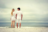 Fototapety A happy young married couple is holding hands and looking at each other as the stand on a white sand beach looking out over the ocean while on vacation.