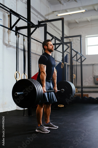 Poster Weightlifter lifting barbells at gym