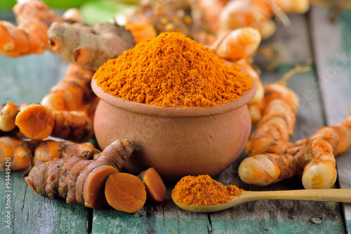 Poster turmeric roots in the basket on wooden table
