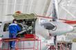 Engineer Aviation Plant repair jet engines in aviation hangar. Aircraft under heavy maintenance. Technician in blue working uniform