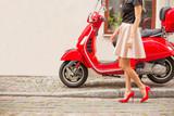 Lady przed czerwonym skuterem moto