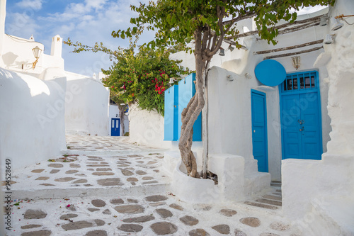 Mykonos traditional white streetview with blue door and trees, Greece