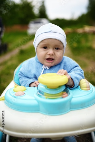 Poster Crying cute baby in baby walker walks outdoors