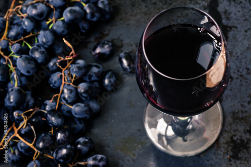 Wineglass of red wine with grapes Poster